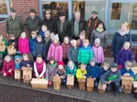 Schülerinnen und Schüler der Ludgerusschule Rhede haben gemeinsam mit den Mitgliedern des Hegerings sowie den Klassenlehrerinnen der Grundschule Nistkästen aufgehangen. Foto: Schule